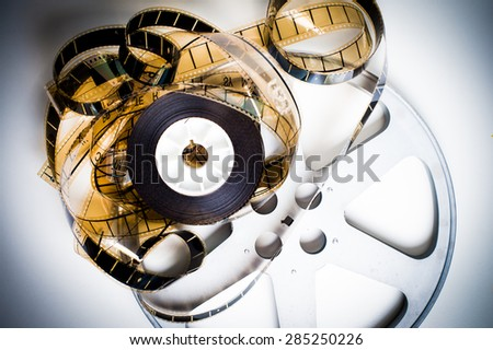 Unrolled 35 mm film on movie reel on white background vintage color effect - stock photo