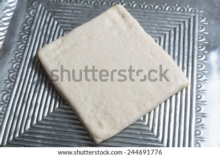 Unrolling dough on metal plate - stock photo