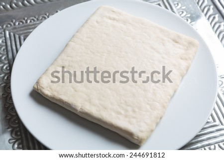 Unrolling dough on white plate on metal plate - stock photo