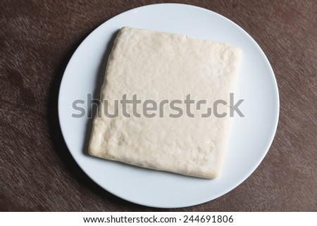 Unrolling dough on white plate on table - stock photo