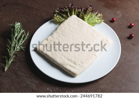 Unrolling dough with salad and rosemarie on plate - stock photo