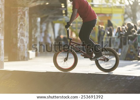 Unseen bmx biker in a skate park with a blurred crowd watching in the sunlight - stock photo