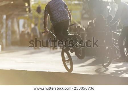 Unseen bmx rider balancing on one wheel  - stock photo