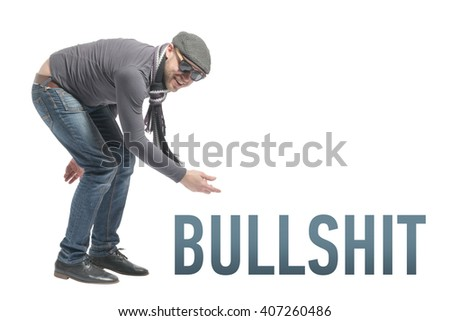 Unshaven bald man wearing a cap, jeans, sunglasses and scarf crouched and points to the inscription BULLSHIT. Isolated - stock photo