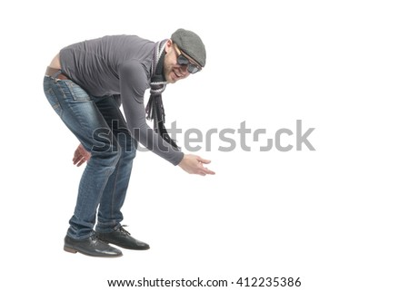 Unshaven bald man wearing a cap, jeans, sunglasses and scarf sat down and points on the empty space. Isolated