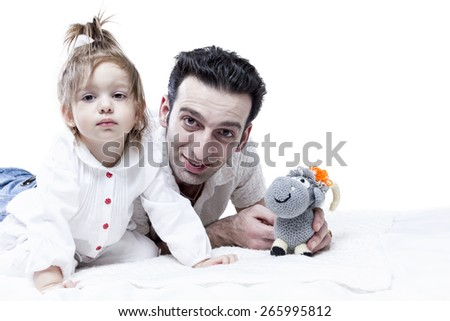Unshaven man lies and playing with baby girl holding soft toy looking at the camera - stock photo