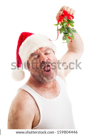 Unshaven middle-aged man in his undershirt, wearing a santa hat and holding mistletoe, waiting for a sloppy wet kiss.  Isolated on white.   - stock photo
