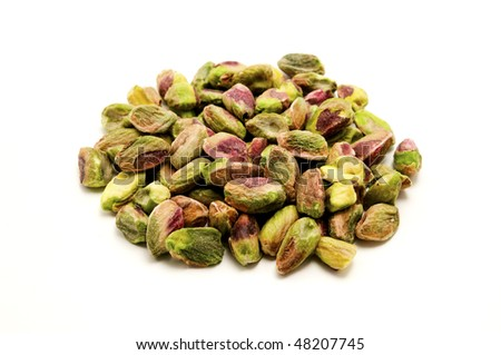 Unshelled roasted pistachios on a white background