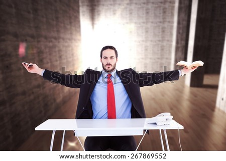 Unsmiling businessman sitting with arms outstretched against abstract room - stock photo