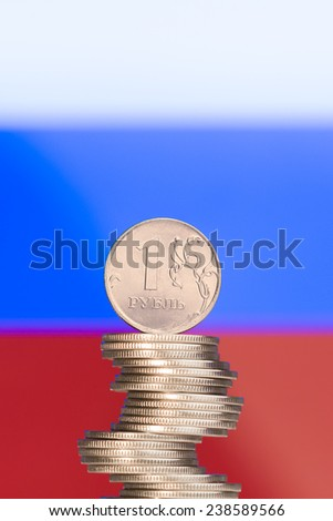 Unstable column of rubles against the Russian flag - stock photo
