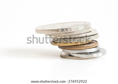 Unstable stack of money coin isolated on white background - stock photo