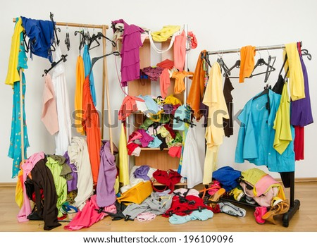 Untidy cluttered woman wardrobe with colorful clothes and accessories. Messy clothes thrown on a shelf, on the ground and off the hangers and racks. - stock photo