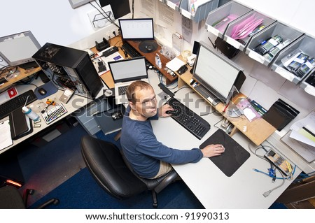 Untidy computer repair shop, with an IT technician working on several computers at the same time - stock photo