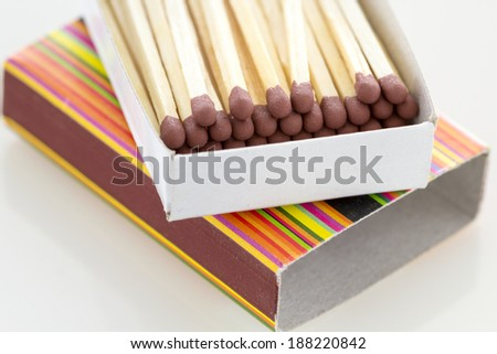 Unused matches with brown head screw in the box on white background with reflexions - stock photo