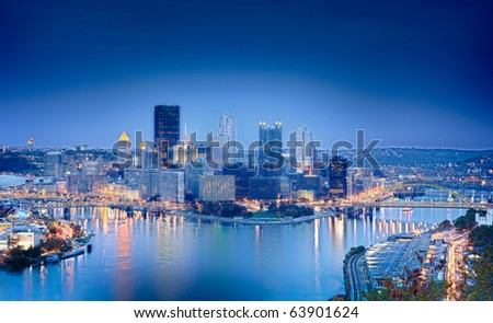 Unusual blue shaded image of Pittsburgh in the evening processed in HDR to highlight the reflections in the river - stock photo