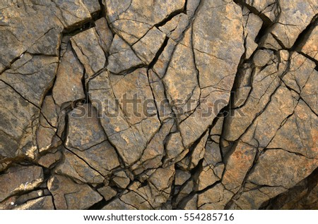unusual cracks in textural brown stone as background