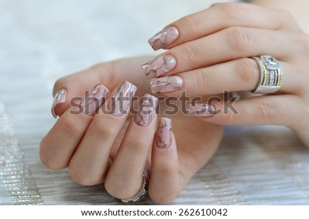 Unusual marble textured nail art design in earthy tones. - stock photo