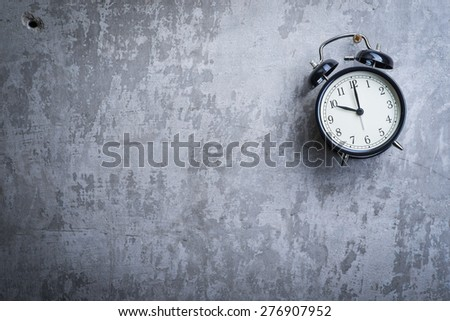 Unusual picture of old vintage alarm clock hanging on the grey concrete wall - stock photo
