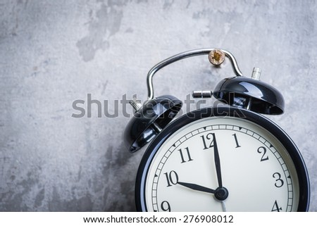 Unusual picture of old vintage alarm clock hanging on the grey concrete wall