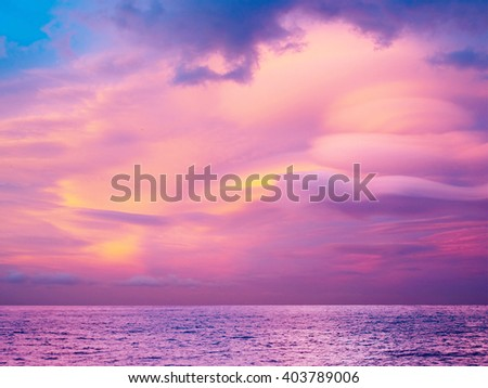 Unusual pink clouds on the sea. - stock photo