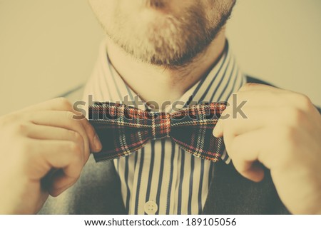 Unusual retro fashion business man with bowtie in hands - stock photo