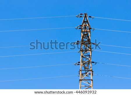 Unusual side view high voltage tower (electricity post) against blue sky. - stock photo