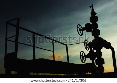 unusual silhouette of gas rig drill, on the background of blue autumn sunset sky, fuel technology industry - stock photo