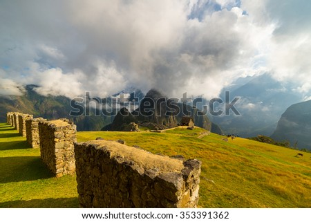 Unusual view of Machu Picchu illuminated by morning sunlight coming out from the opening clouds. The Inca's city is the most visited travel destination in Peru. Wide angle view from above. - stock photo