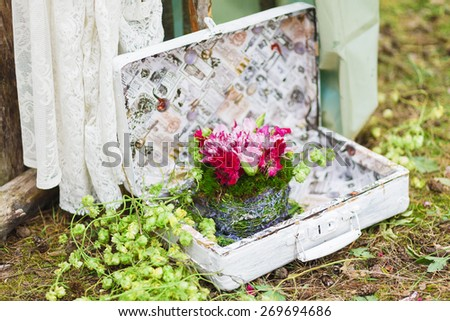 Unusual wedding floral decor composition - flowers in suitcase - stock photo