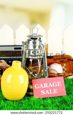 Unwanted things ready for a garage sale, on green grass - stock photo