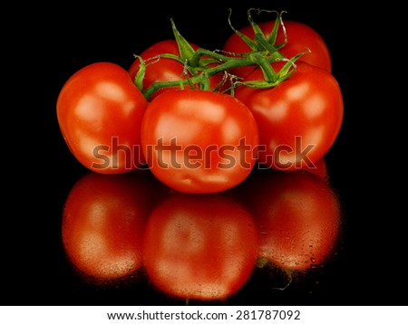 Unwashed tomatoes on a black background with reflection - stock photo