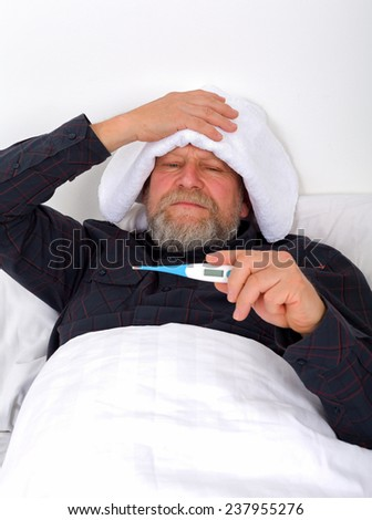 Unwell elderly man lying in the bed with a thermometer - stock photo