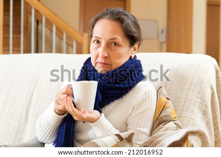 unwell woman in scarf sitting at home - stock photo