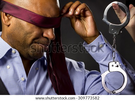 Unwilling male forced by girlfriend to sexual BDSM role playing.  The man is blindfolded and a female hand is holding hand cuffs.  The image depicts sexual fetish with no nudity.