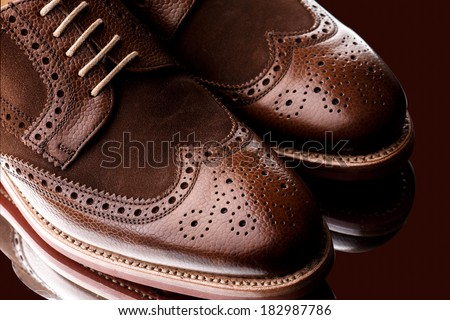 Unworn, laced pair of two tone men brogues (derbies) with elegant toe shape. The upper is stunning combination of brown calf with brown suede. Isolated on dark brown background with mirror reflection. - stock photo
