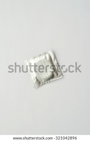 Unwrapped condom isolated on a white background - stock photo