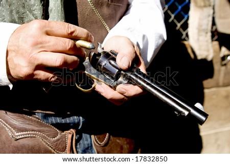 Up-close horizontial photo loading bullets into a handgun - stock photo