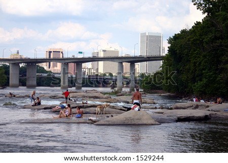 Up River View of Downtown Richmond Virginia - People Sitting on Rocks - stock photo