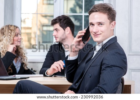 Up to a client of a businessman in office. Businessman talking on a cell phone while his colleagues talking in the background sitting at table - stock photo