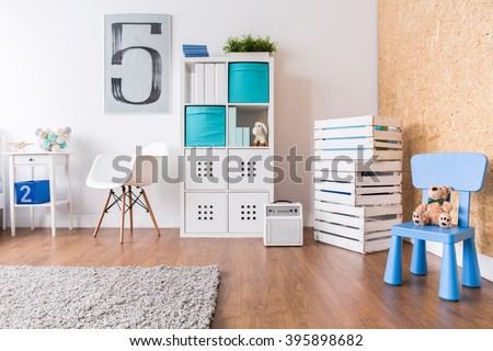 Up-to-date decor of child's room with wooden parquet and white furniture - stock photo