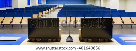 Up-to-date lecture hall with two new generation computers on professor's desk - stock photo