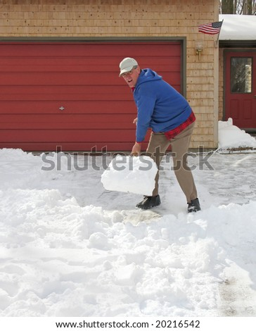 Upbeat man shoveling snow - stock photo