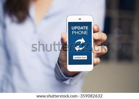 Update phone message in a mobile screen. Woman showing a mobile phone. - stock photo