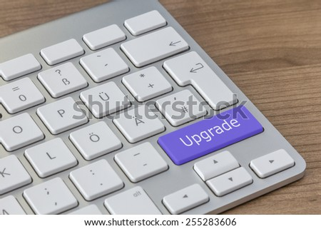 Upgrade written on a large blue button of a modern keyboard on a wooden desktop