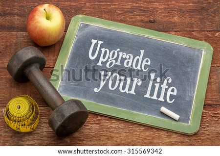 upgrade your life concept -  text on slate blackboard against weathered red painted barn wood with a dumbbell, apple and tape measure - stock photo