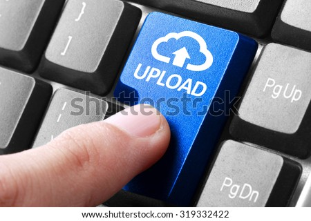 Uploading file. gesture of finger pressing upload button on a computer keyboard - stock photo