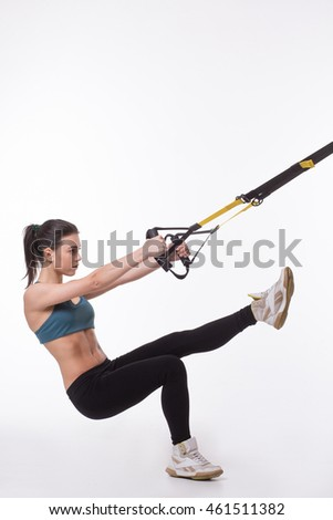 Upper body exercise concept. Picture of young woman using suspension trainer sling for exercising her body. TRX concept. Studio shot.