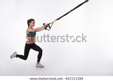 Upper body exercise concept. TRX concept. Studio shot. Image of young beautiful woman training with suspension trainer sling isolated on white background.
