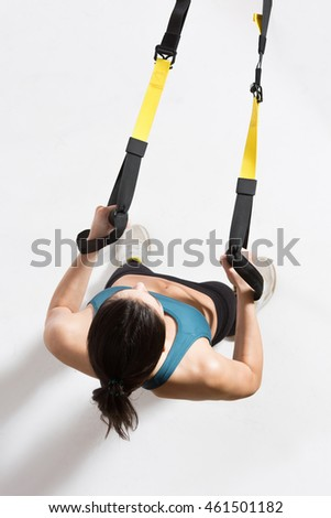 Upper body exercise on TRX isolated on white. Top view of fitness trainer lady exercising on suspension trainer sling or suspension straps in studio.