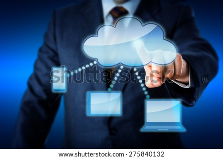Upper body of a business man in blue suit is touching a blank cloud icon at the heart of a smart computing network. Cell phone, tablet computer and laptop are all linked to the cloud. Copy space.